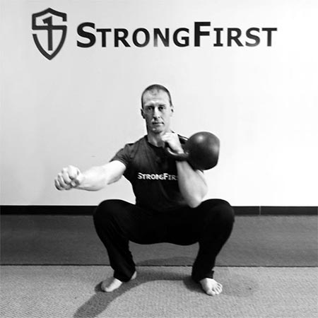 Alexey Senart performing the kettlebell front squat