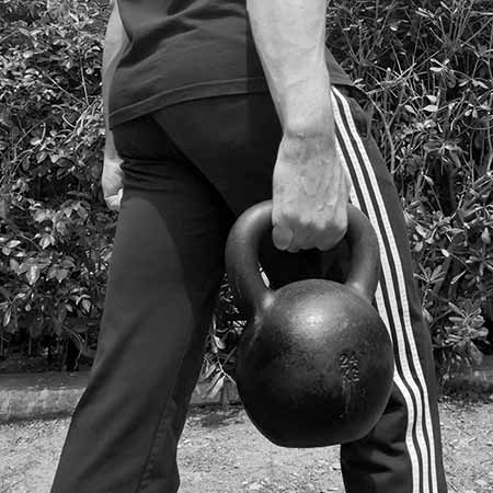 Man performing kettlebell suitcase carry
