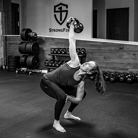 Catherine Buck Le performing the kettlebell bent press