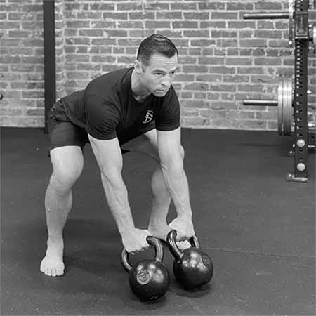 Tony Gracia performing the setup for the double kettlebell clean