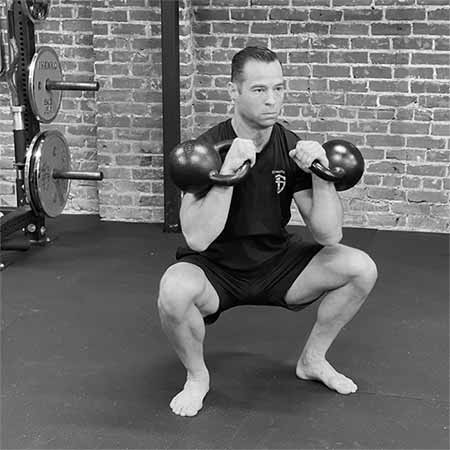 Tony Gracia performing the double kettlebell front squat